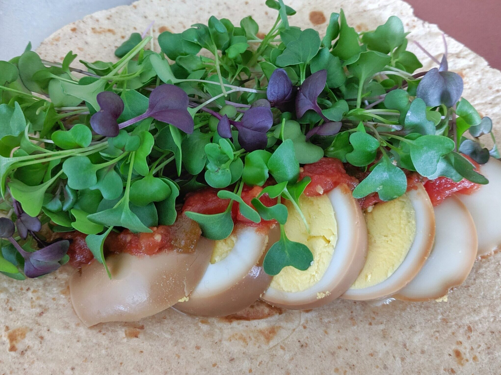 boiled egg and microgreens on a tortilla
