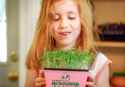 Girl with tray of microgreens